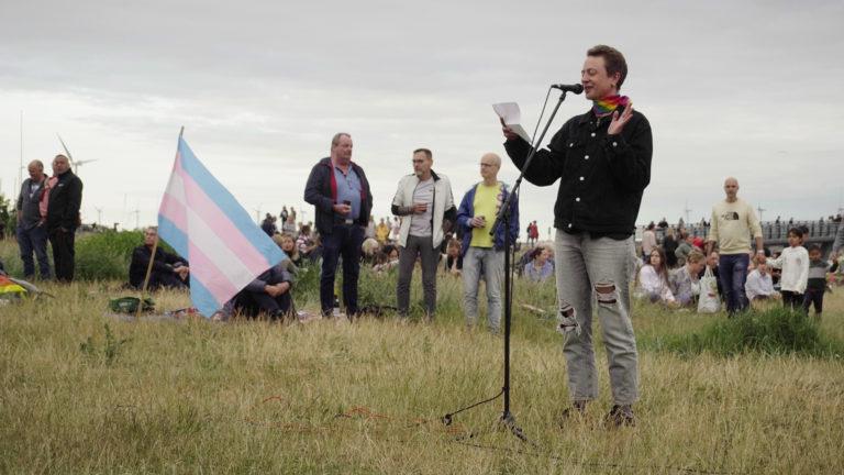 Rei McKay Mansa holdet tale på en græsplæne ved siden af et Trans Pride flag.